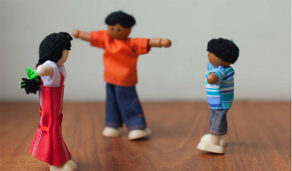 3 knitted dolls placed on a wooden table